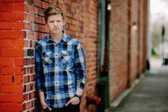 Un hombre joven del handsom se inclina contra una pared de ladrillo en un callejón. Imágenes de archivo libres de regalías