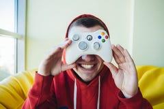 Un hombre joven demuestra una palanca de mando para el videojuego que se sostiene en el nivel del ojo El concepto de videojuegos Fotos de archivo libres de regalías