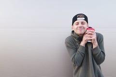 Un hombre joven divertido que abraza una taza de café en un fondo ligero Foto de archivo libre de regalías