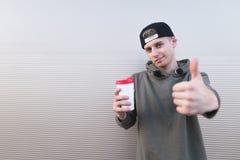 Un hombre joven elegante con una taza de café en sus manos muestra los pulgares para arriba en un fondo ligero Imagenes de archivo