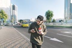 Un hombre joven elegante con una taza de café en sus manos va a lo largo de la acera y utiliza un teléfono móvil Un estudiante es Fotografía de archivo libre de regalías