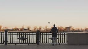 Un hombre joven, elegante vestido hace una pausa el río y mira cuidadosamente en la distancia, agarrando la verja almacen de metraje de vídeo