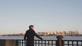 Un hombre joven, elegante vestido hace una pausa el río y mira cuidadosamente en la distancia, agarrando la verja metrajes