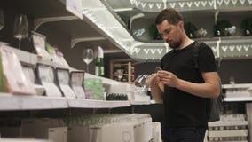 Un hombre joven elige los vidrios hermosos en la alameda para su nuevo apartamento metrajes