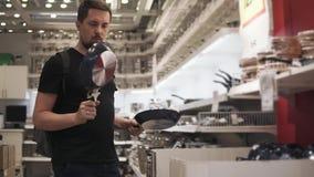 Un hombre joven elige un sartén en la tienda para cocinar la comida en ella metrajes