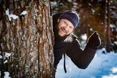 Un hombre joven en un bosque del invierno mira hacia fuera de detrás un árbol y agita su mano foto de archivo