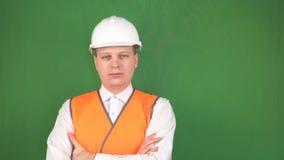 Un hombre joven en un casco blanco del chaleco y de la construcción de la señal es permanente y de mirada del camreu, fondo, chro almacen de video