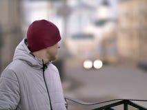 Un hombre joven en un casquillo rojo se est? colocando en la calle que mira detr?s fotografía de archivo libre de regalías