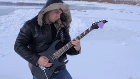 Un hombre joven en el invierno para tocar la guitarra metrajes