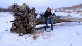 Un hombre joven en el invierno para tocar la guitarra almacen de metraje de vídeo