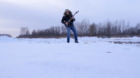 Un hombre joven en el invierno para tocar la guitarra almacen de video