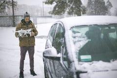 Un hombre joven en el invierno se coloca cerca del coche y sostiene el abejón foto de archivo libre de regalías