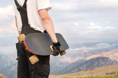 Un hombre joven en guantes que llevan de un casco con un tablero en sus manos y vestido en soportes combinados en un alto del pre Fotos de archivo