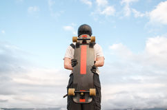 Un hombre joven en guantes que llevan de un casco con un tablero en sus manos y vestido en soportes combinados en un alto del pre Fotografía de archivo libre de regalías