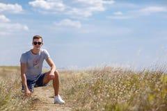 Un hombre joven en los campos Un adolescente relajante que se sienta en un fondo natural Concepto saliente de la forma de vida Co Imagenes de archivo