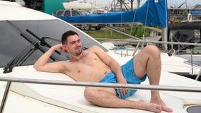 Un hombre joven en mentiras y morenos de los pantalones cortos en un barco almacen de metraje de vídeo