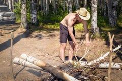 Un hombre joven en pantalones cortos y un sombrero en naturaleza enciende un fuego fotografía de archivo libre de regalías