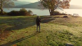 Un hombre joven en un parque que toma las fotografías del océano en la salida del sol almacen de metraje de vídeo