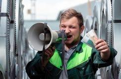 Un hombre joven en ropa de trabajo grita en alta voz en un altavoz que invita para unirse a lo en el trabajo El hombre sostiene h imagen de archivo libre de regalías