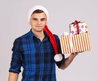 Un hombre joven en sombrero del ` s de Papá Noel sostiene los regalos con una mano en el peso imagen de archivo
