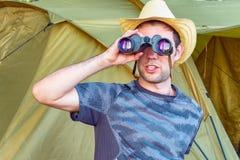 Un hombre joven en un sombrero que mira a través de los prismáticos Hombre joven que se sienta en naturaleza cerca de la tienda imágenes de archivo libres de regalías