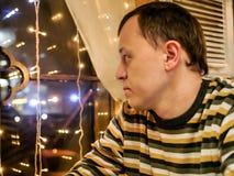 Un hombre joven en un suéter rayado se sienta por la tarde en un café mira hacia fuera la ventana fotos de archivo libres de regalías