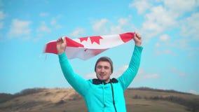 Un hombre joven en un suéter y un sombrero azules sostiene la bandera canadiense en su mano almacen de metraje de vídeo
