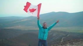Un hombre joven en un su?ter y un sombrero azules sostiene la bandera canadiense en su mano almacen de video