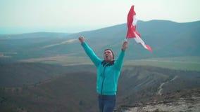 Un hombre joven en un su?ter y un sombrero azules sostiene la bandera canadiense en su mano almacen de metraje de vídeo