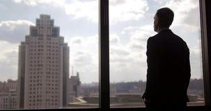 Un hombre joven en un traje camina encima a una ventana panorámica y disfruta de la vista de la ciudad Windows, paisaje urbano, r almacen de metraje de vídeo