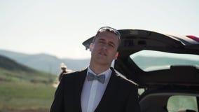 Un hombre joven en un traje clásico, corbata de lazo fuma VAPE Soportes al lado del coche en naturaleza almacen de metraje de vídeo