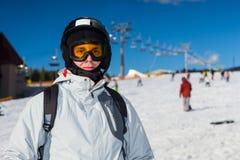 Un hombre joven en traje de esquí, con el casco y las gafas del esquí colocándose adentro Imagen de archivo libre de regalías