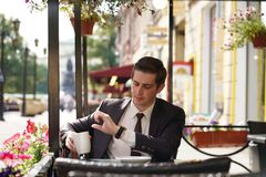 Un hombre joven en un traje de negocios negro, una camisa blanca y un lazo mira el reloj foto de archivo