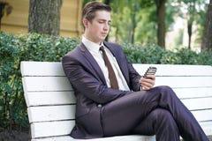 Un hombre joven en un traje de negocios salió de la oficina y vino al parque él se sienta en un banco blanco solamente y habla en imagenes de archivo