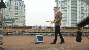 Un hombre joven en un traje se acerca al monitor con un palo y y se prepara para romperlo Palo, violencia, odio, anarquía almacen de metraje de vídeo