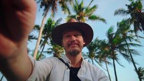 Un hombre joven en un sombrero con el bigote entre las palmas de coco guarda la cámara o el teléfono en sus manos, se tira y metrajes