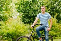 Un hombre joven en una bicicleta mira en la distancia Imágenes de archivo libres de regalías