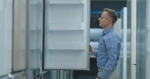 Un hombre joven en una camisa azul para abrir la puerta del refrigerador en la tienda de dispositivos y a comparar con otros mode almacen de metraje de vídeo