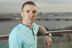 Un hombre joven en una camisa de la turquesa, manga corta, retrato contra la perspectiva de una ciudad europea. Una persona, varón Fotografía de archivo libre de regalías
