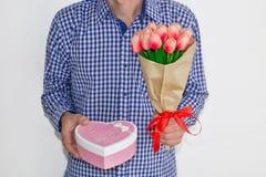Un hombre joven en una camisa de tela escocesa azul y vaqueros, sosteniendo un ramo de tulipanes y de una caja de regalo en la fo foto de archivo