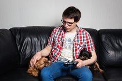 Un hombre joven en una camisa roja y tejanos se sienta en casa y juega a los videojuegos así como su perro El individuo llevó una fotografía de archivo libre de regalías
