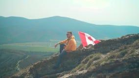 Un hombre joven en una chaqueta amarilla, tejanos y vidrios se sienta en un canto, seguido por la bandera de Canadá almacen de video