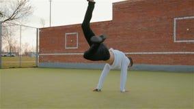 Un hombre joven en una chaqueta blanca y pantalones negros que bailan con eficacia el breakdance inferior en el patio almacen de metraje de vídeo