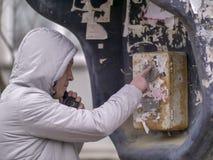 Un hombre joven en una chaqueta gris con una capilla está llamando de un teléfono público viejo en la calle foto de archivo libre de regalías