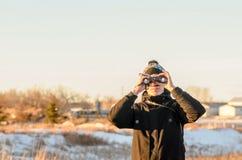 Un hombre joven en una chaqueta negra, miradas a través de los prismáticos en el w fotos de archivo libres de regalías