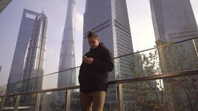 Un hombre joven en una chaqueta negra utiliza un teléfono en el fondo de rascacielos en Shangai, China almacen de video