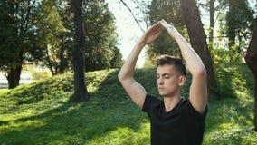 Un hombre joven en una hierba verde de Lotus Position Sitting On The en el parque el concepto de calma y de meditaci?n Cierre par almacen de video