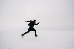 Un hombre joven en una mochila negra y el viajar en la charca congelada Fotografía de archivo libre de regalías