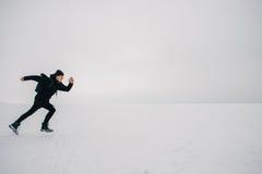 Un hombre joven en una mochila negra y el viajar en la charca congelada Foto de archivo