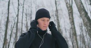 Un hombre joven en una sacudida de la mañana sostiene los auriculares en sus manos y los inserta en sus oídos antes de correr en  almacen de metraje de vídeo